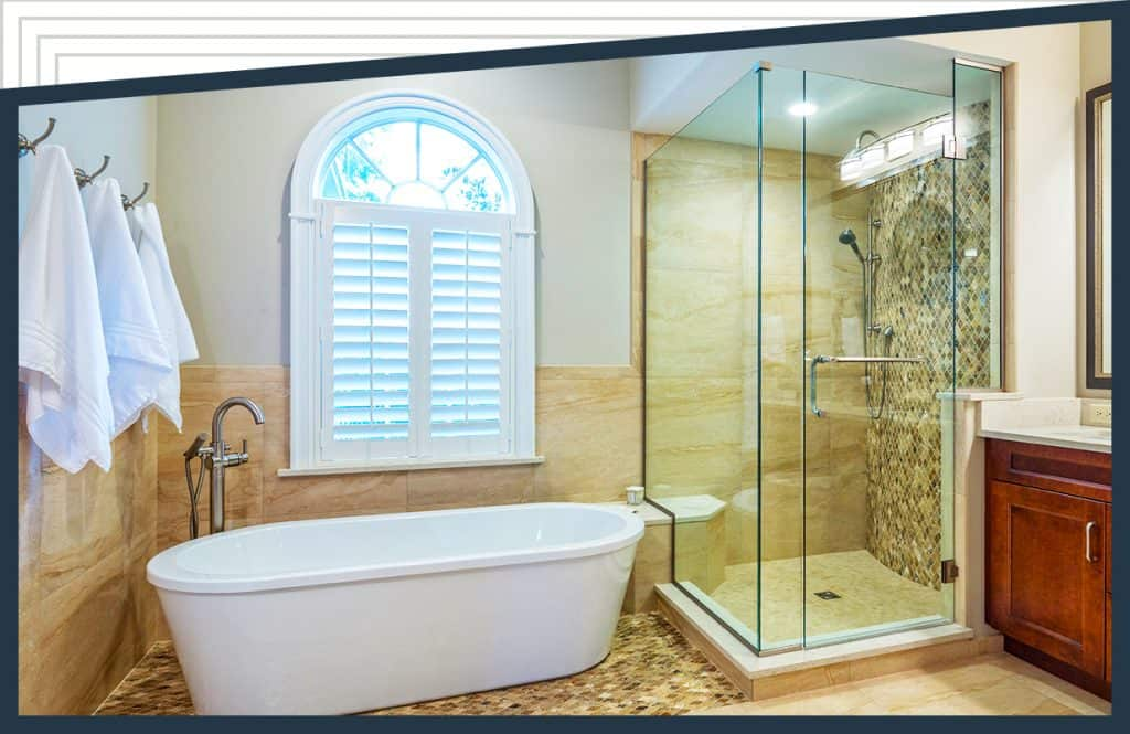 A bathtub underneath a window with towels hanging nearby. An Aldora glass corner shower with Peterson Shower Doors is next to the sink and vanity.