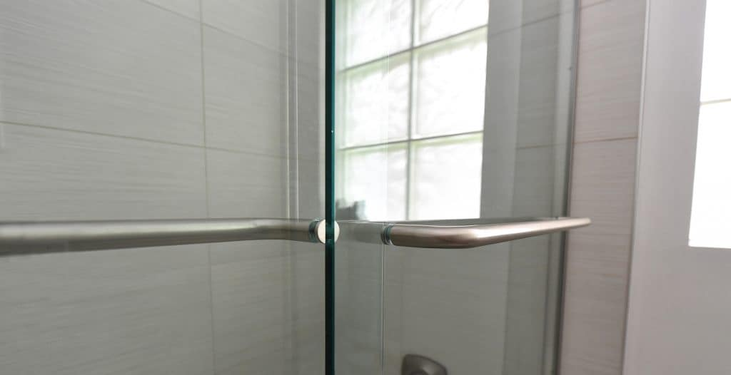 Close up view of chrome shower bar attached to glass shower door by Aldora, slate grey tile and chrome water controls in background