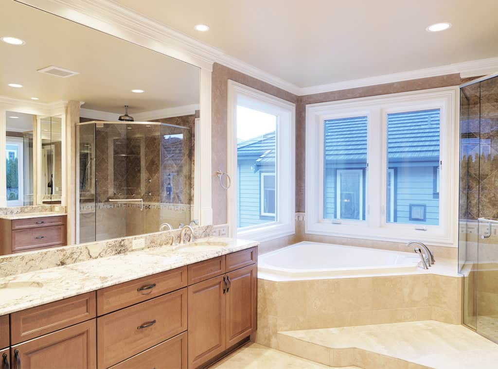 A bathtub is in the corner of the bathroom under windows. An Aldora mirror, sinks and a vanity cover the left wall. A walk-in glass shower is seen in the mirror reflection.