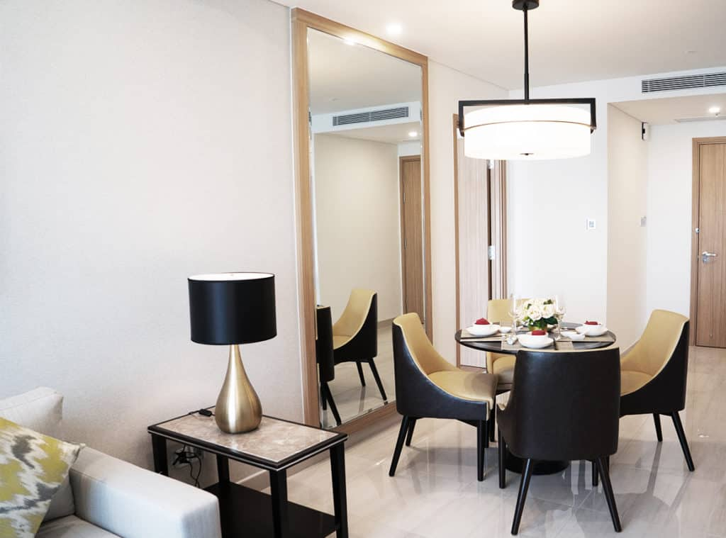 A set dining table with four chairs sits under a ceiling lamp, in front of a foyer and door. A floor to ceiling Aldora mirror covers the wall to the left of the table. A side table with a lamp sits next to a couch.
