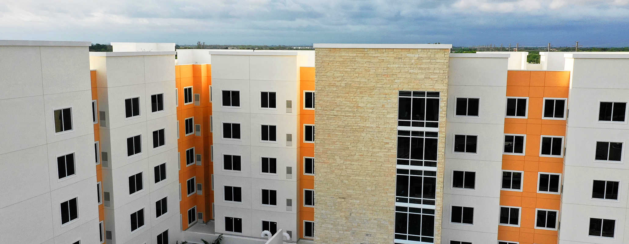 Multi-level orange building with grey outsets and stone accents, FS-300 Impact front set double panel windows with aluminum framing by Aldora, grid curtain wall windows in stone accent section of building