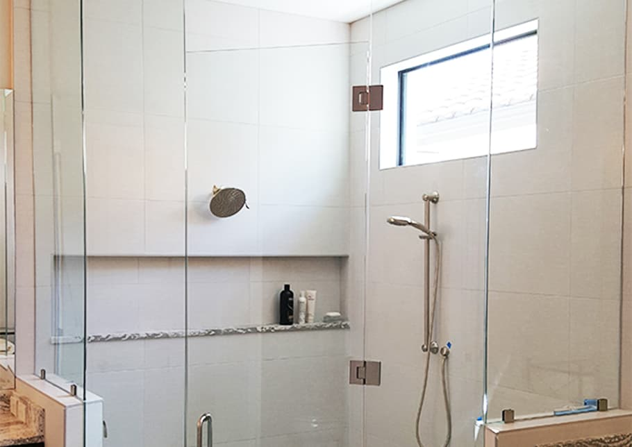 A shower enclosed in Aldora custom glass including the door. The tiled wall holds faucets, a shower head, a shelf and a window