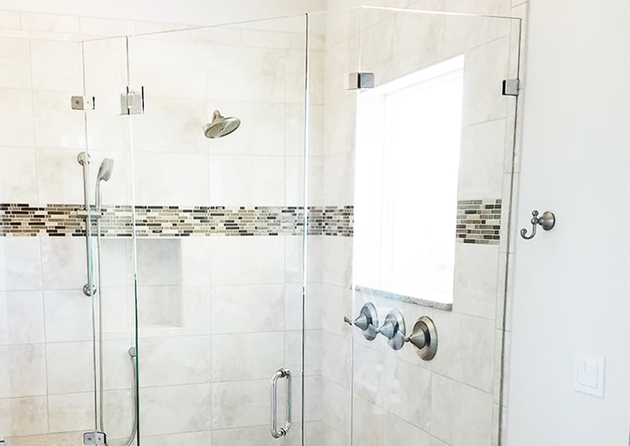 A shower enclosed in Aldora custom glass including the door. The tiled wall holds faucets, a shower head and a window