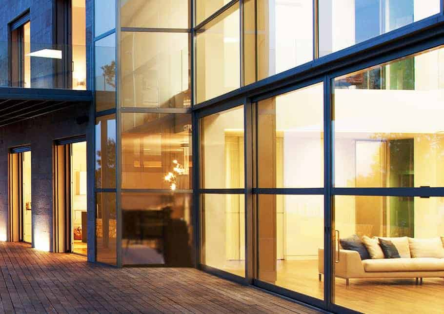 An exterior view of RapidGlaze Aldora glass walls, a brick pavement runs in front of the building, a night view