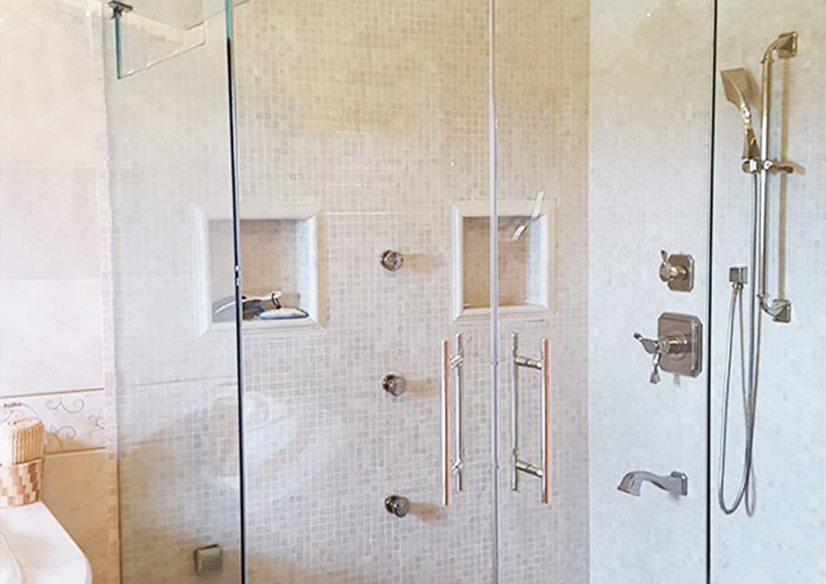 A glass enclosed shower features Aldora towel bars and handles, tiled walls, and faucets