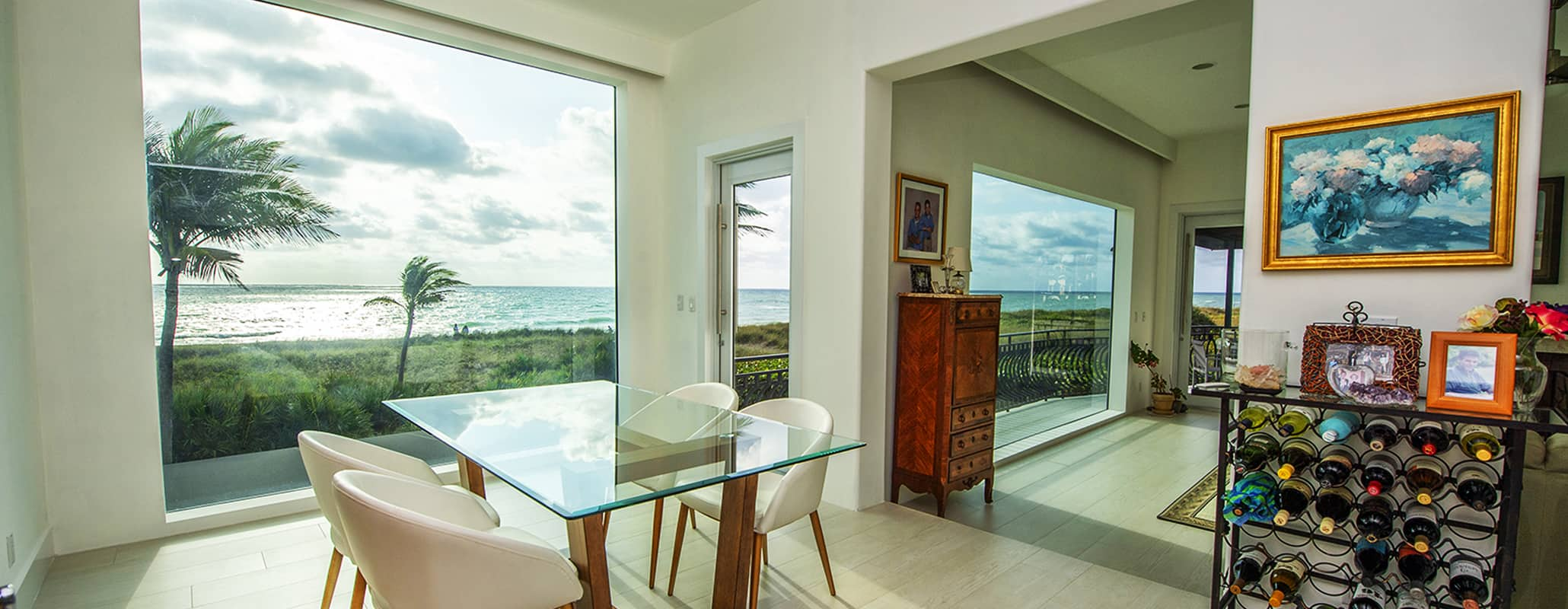 Dining room with glass table, 4 chairs, wine bar, looking out floor-to-ceiling FS-300 Maxi View Impact Storefront System by Aldora, modern interior design, ocean view through impact window